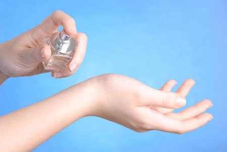 eau de toilette: Woman spraying perfume to her wrist Stock Photo