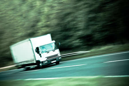 courier: Goods vehicle on road with speed blur and processed colour effect