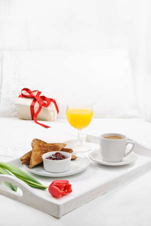 glass bed: Breakfast in bed with gift left on the pillow - high key, Stock Photo
