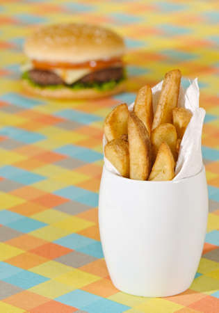 un healthy: Chunky chips with burger in background on bright checkered tablecloth