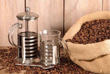 Cafetiere of coffee with cup and burlap sack of beans photo