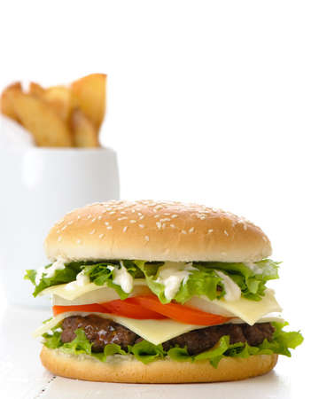 Hamburger with fries in background on white table photo