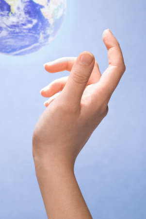 woman's: Hand reaching out towards the earth