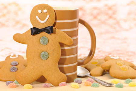 Gingerbread man with bow tie against mug with further smaller men lying by his sides photo
