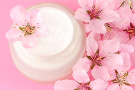 moisturiser: Pot of face moisturiser cream surrounded by flower petals