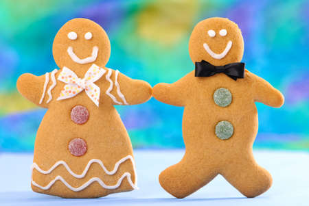Homemade gingerbread couple holding hands in blue setting Stock Photo