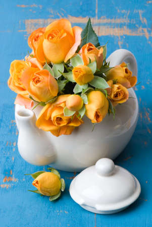 wooden lid: Freshly picked orange garden roses in teapot on rustic table