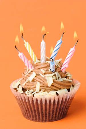 Fun g�teau d'anniversaire au chocolat avec des bougies de couleur sur fond orange Banque d'images - 4655549