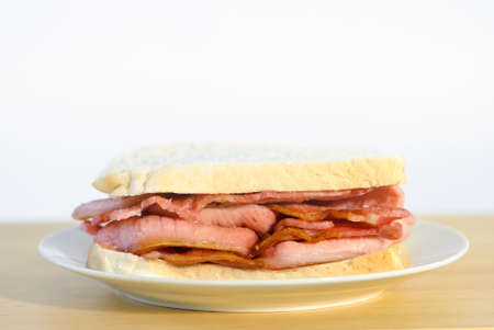 Juicy bacon sandwich on white plate ready to eat photo