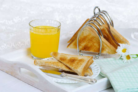 Breakfast with toast in rack and on plate with orange juice photo