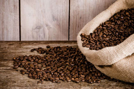 Burlap sack of coffee beans in rustic setting  photo
