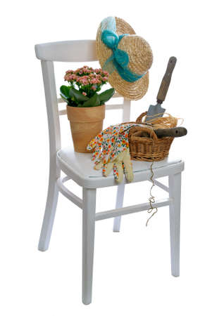 Rustic white chair laden with garden tools and straw hat photo
