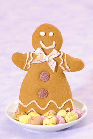 Gingerbread lady in a dish of speckled chocolate eggs on a lilac background photo