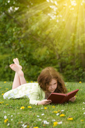 Young girl reading a book outdoors in summertime photo