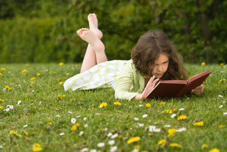 engrossed: Young girl reading a book in a grassy meadow covered with wild flowers