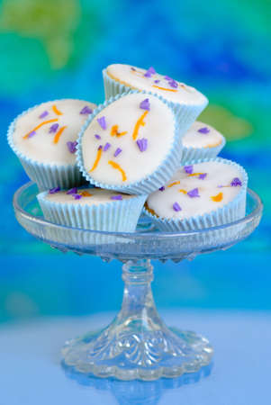 Pretty cupcakes on glass comport dish decorated with lavender and orange zest photo