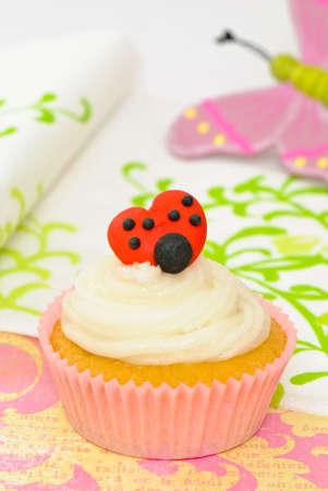 Sponge cupcake with frosted icing and ladybug decoration  photo