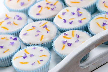 Tray of iced cupcakes decorated with orange zest and lavender petals Stock Photo - 4779313