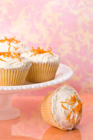 sprinkled: Sponge cupcakes with butter cream frosting and orange zest topping on white stand Stock Photo