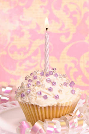 Decorated party cupcake with white lit candle and streamers Stock Photo