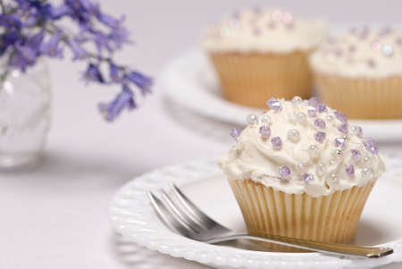 Pretty cupcakes decorated with purple sprinkles, vase of bluebell flowers in background