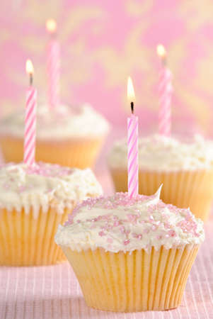 Party cupcakes with pink striped lit candles photo