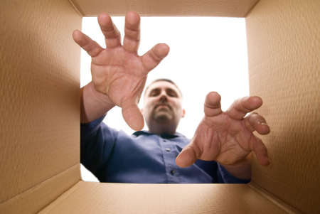 grabbing hand: Person unpacking (or packing) a cardboard carton Stock Photo