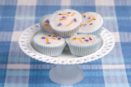 Cake stand filled with cupcakes decorated with lavender and orange zest Stock Photo - 4843292