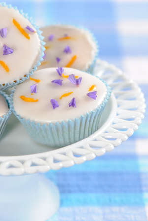 Pretty iced cupcakes displayed on glass stand  Stock Photo - 4843297