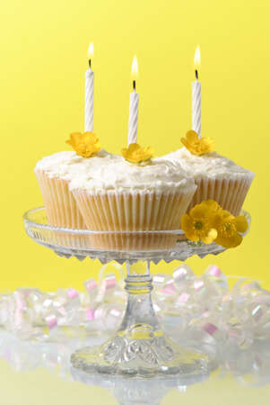 Glass comport of buttercup fairy sponge cakes with lit candles photo