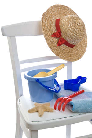 implements: Rustic white chair loaded with childs play items for day at the beach