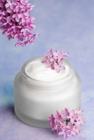 blue toned: Pot of moisturizing cream with lilac flowers and blue toned background