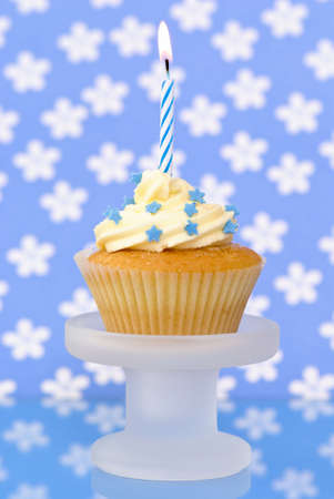 Birthday cupcake decorated with blue stars on glass comport photo