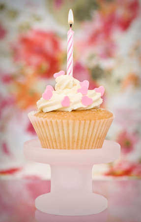 Pink cupcake decorated with heart sprinkles - shallow depth of field, focus on candle photo