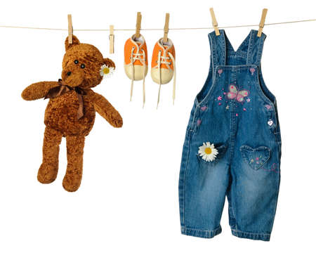 Teddy bear on washing line with sneakers and dungarees photo