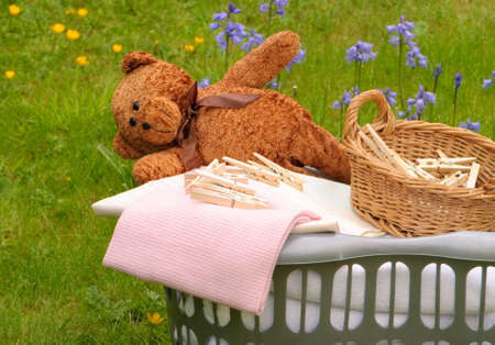 Wash day with basket of laundry, pegs and teddy bear photo