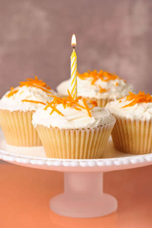 ice cream stand: Comport of cupcakes with orange zest, one cake with lit candle Stock Photo