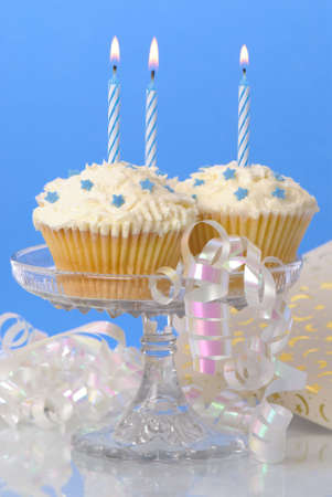 Cupcakes on glass stand with lit candles and streamers, gift in background photo