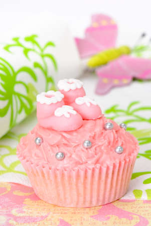baptism background: Pink cupcake with sugar baby booties Stock Photo