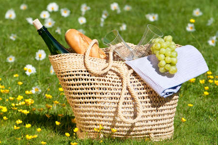 wicker: Picnic basket packed with wine, glasses, grapes etc. in flower meadow