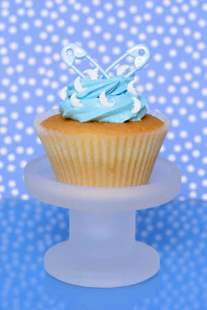 Birth of a boy cupcake on stand with diaper pins - blue spotty background photo