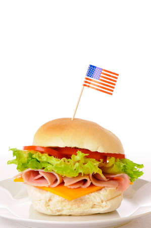 freshly prepared: Freshly prepared ham & cheese salad crusty white roll on white plate with American flag Stock Photo