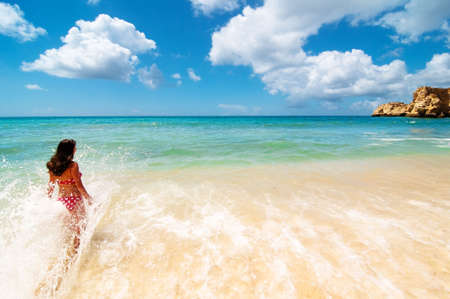 go for: Girl splashing in the water at a tropical beach paradise