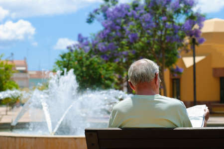 engrossed: Senior male reading his newspaper on bench overlooking fountain in Silves square