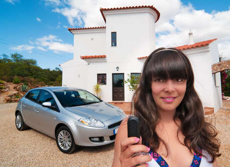 Young woman given keys to luxury property and car photo