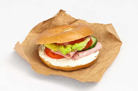 Ham and cheese bagel with salad in brown paper wrapping Stock Photo - 5033826