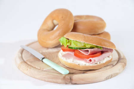 Ham bagel on rustic board with further bagels in background Stock Photo - 5033828