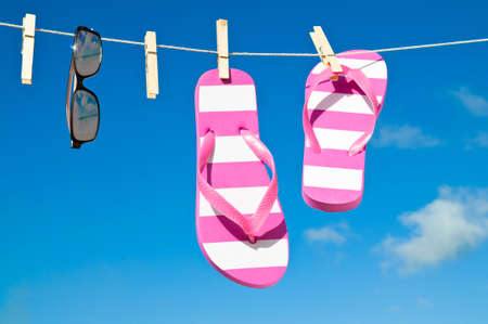 sunshades: Holiday washing line against blue sky with flip flops and sunshades - reflection of beach in sunglasses