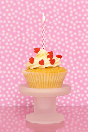 Cupcake decorated with red heart sprinkles on pink spotty background photo