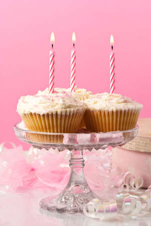 Birthday cupcakes with red striped lit candles with present and streamers in background photo